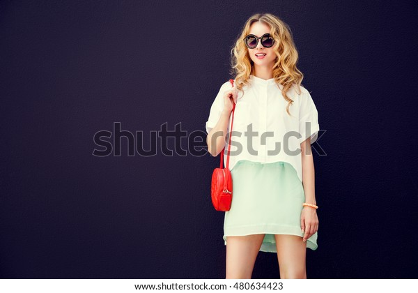 Trendy Girl in Sunglasses at the Dark Textured Wall Background. Urban Fashion Woman Concept in Summer. Street Style. Toned Photo with Copy Space.