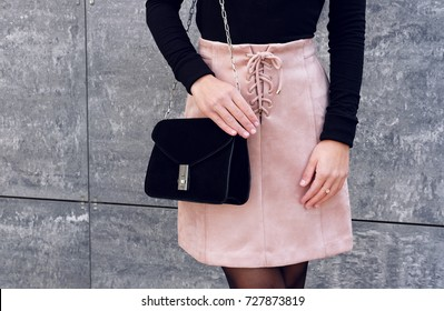 Trendy girl wear pink suede lace up skirt with black little bag near gray wall