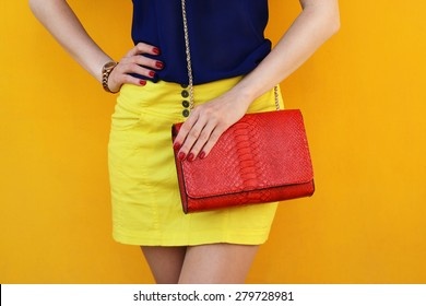 Trendy girl in yellow skirt with red leather bag . Stylish outfit and fashion concept