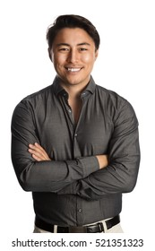 A trendy good looking man wearing a grey shirt standing against a white background relaxing.