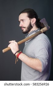 Trendy guy with a beard and mustache, holding an ax in his hands. Bearded woodcutter. battle ax on his shoulder