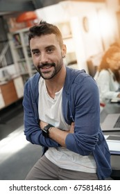 Trendy guy in coworking office with arms crossed