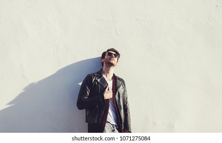 Trendy guy with leather jacket and eyeglasses standing by wall. copyspace