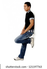 Trendy guy standing against the wall and smiling