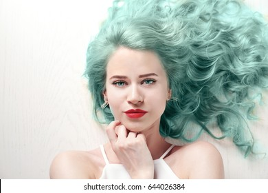 Trendy hairstyle ideas. Young woman with mint hair color on wooden background