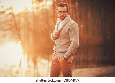 Trendy handsome man posing in autumn park alone