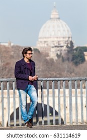 Trendy handsome young boy leaning on the railing of a bridge in the historic center of Rome in Italy. Wearing a jacket and jeans, eyeglasses and phone in hand. Behind him the basilica of Saint Peter.