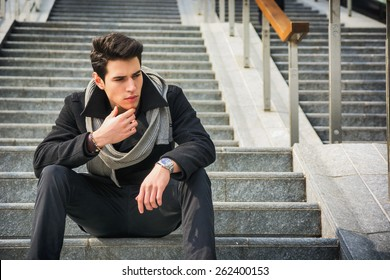 Trendy handsome young man in winter fashion sitting on a long staircase leading to an urban commercial building looking to a side with a serious expression