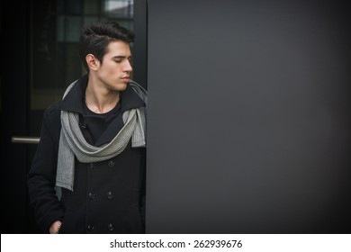 Trendy handsome young man in winter fashion standing against wall in urban environment looking at copyspace