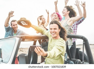 Trendy happy friends taking selfie with smartphone in desert on convertible jeep car - Travel people having fun together in excursion - Friendship and vacation concept - Focus on man's face with phone