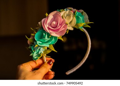 trendy headband with flowers. Girls fashion.flower crown.floral headband. tiara of artificial flowers isolated on black background.joyful hair accessories . Selective focus.Copy space