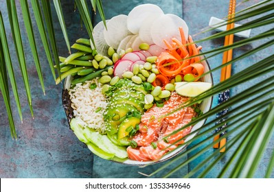 Trendy healthy food.Poke bowl with salmon, avocado, edamame beans, vegetables and rice. Sushi bowl. Turquoise background and palm leaves sun light top view.