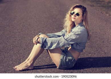 Trendy Hipster Girl Sitting on the Road. Toned Photo. Modern Youth Lifestyle Concept.