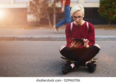 Trendy hipster girl waiting for feedback on her streaming video of skating via touchpad while sitting on board on city street near background with copy space area for your advertising text messages