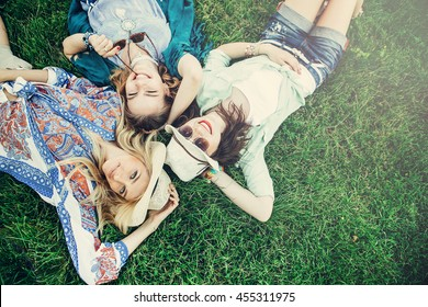 Trendy Hipster Girls Relaxing on the Grass . Summer lifestyle portrait of three hipster women laying on the grass enjoy nice day, wearing bright sunglasses. Best friends girls having fun, joy.