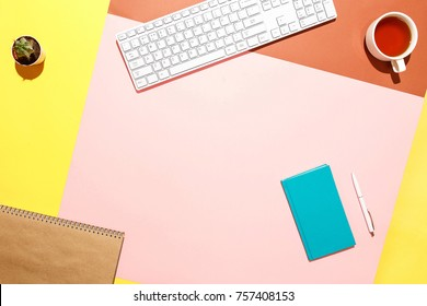 Trendy home office workspace. Flat lay composition of keyboard, cactus, diary with pen and cup of tea on colorful desk. Pink, yellow, aquamarine and and brown colours. Blogger's home office.