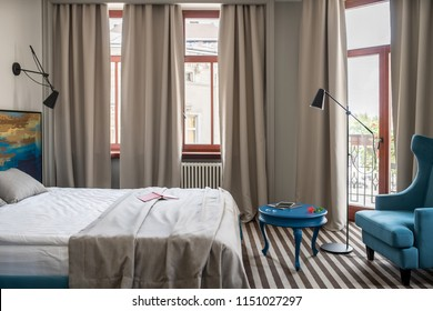 Trendy hotel room with light walls and a striped floor. There is a double bed with a colorful wooden bedhead, round blue table with an armchair, windows with curtains, door to the balcony, floor lamp.