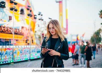Trendy influencer or modern millennial hipster teenager or cool fashion woman stands in center of country fair or carnival or festival, uses smartphone application to stay connected on social media