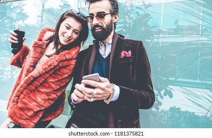 Trendy influencers people using smartphone social media app - Young fashion couple watching story video on mobile phone - Technology trends, marketing and new digital job concept - Focus on man face