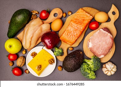 Trendy ketogenic diet products set. Paleo, pegan low carbs nutrition. Meat, fish, cheese, fruits and vegetables. Black stone concrete background
