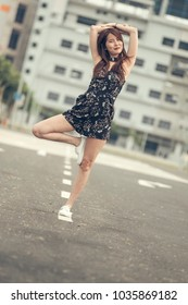 Trendy lady with nice dimples arms above head stand on middle of road with building background.