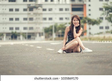 Trendy lady with nice dimples legs crossed sit on road with building background.