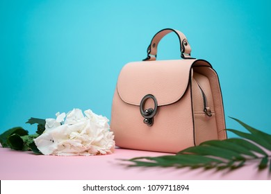 Trendy light brown leather female bag on the pink surface on the cyan background in the studio. There is a green branch and white flowers next to it. Closeup. Horizontal.