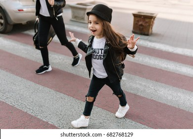 Trendy little schoolgirl walks along the pedestrian crossing after school in good mood. Portrait of joyful kid with long dark hair in cool white sneakers running on crosswalk.
