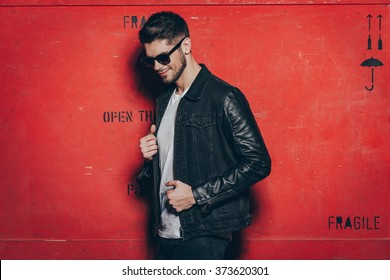 Trendy look. Handsome young man in sunglasses adjusting his jacket and looking away with smile while standing against red background