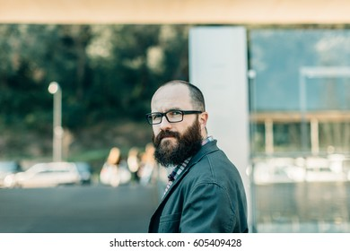 Trendy man in glasses looking seriously at camera on of street.