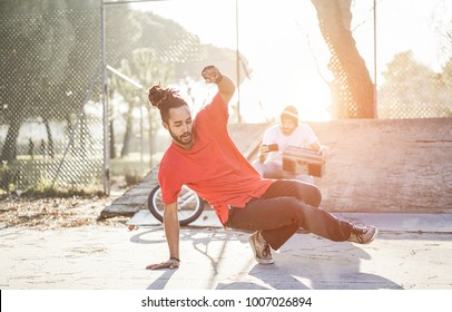 Trendy man making video feed of his breakdancer friend dancing in city park outdoor - Young people having fun sharing media online - Focus on dancer face - Youth lifestyle and friendship concept