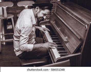 Trendy man with stylish hat and beard trying playing vintage old wooden piano - Young artist performing in cocktail bar - Black and white editing - Focus on ear eye - Warm contrast filter