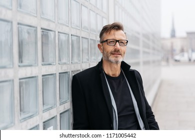 Trendy middle-aged man deep in thought standing in a city square leaning on a glass brick wall looking up with a pensive expression