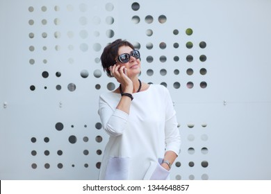 Trendy middle-aged woman wearing white blouse or dress and black sunglasses is speaking on smartphone cheerfully standing on street near a metallic stand smiling happy looking to side up thoughtful.