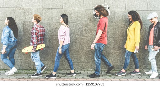 Trendy millennials people walking outdoor holding stereo, cruiser skateboard, vintage camera and smartphones - Young happy friends having fun together outdoor - Focus on center man face