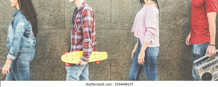 Trendy millennials people walking outdoor holding boombox stereo, cruiser skateboard and smartphone - Young happy friends having fun together outdoor - (0's lifestyle concept - Focus on hands