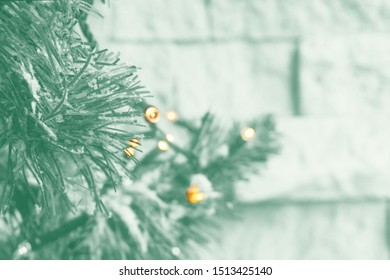 Trendy mint colored closeup of holiday fir garland with lights on the background of brick wall. Concept of winter and Christmas decoration. Toned image.