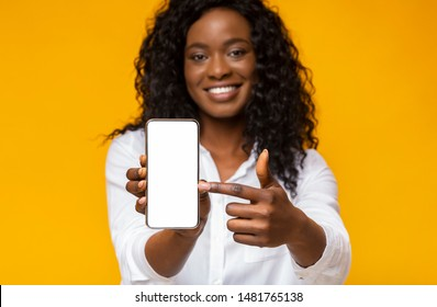 Trendy mobile phone. Smiling african american woman holding latest slim smartphone with blank screen and pointing at it.