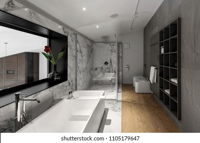 Trendy modern bathroom with white and tiled walls. There is a large white bath with chrome faucet, window with flower in vase, dark shelves, glass shower cabin, toilet, bidet, luminous lamps.