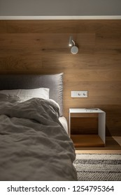Trendy modern bedroom with a wooden wall and a parquet with carpet on the floor. There is a bed with a light pillow and blanket, hanging luminous lamp, nightstand with a cellphone and earphones.