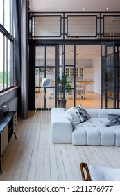 trendy modern design two-level  apartment with large high windows. The stylish living room and kitchen in bright colors are undressed by a glass partition. bedroom on the second floor.