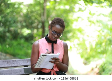 Trendy modern ethnic woman looking concentrated on writing in notepad sitting in solitude on bench in park
