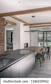 Trendy modern interior with white and brick walls and a ceiling with wooden beams. There is a kitchen island, table with chairs, chandelier, sofas, fireplace, doors, terrace with armchairs outdoors.