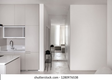 Trendy modern kitchen with light walls and a gray floor. There is a kitchen island, sink, faucet, corner sofa, windows with curtains, black stand with a bag, door, long mirror. Horizontal.