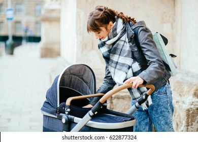 Trendy modern mother on a city street, urban landscape. Young mother walks with a child in the city. Beautiful young woman with a child.
