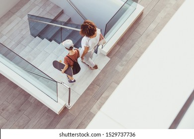 Trendy mother and son walking on stairs in a modern city context. Young boy with skateboard goes down the ladder with mum Top view of people walks in a new mall. Family scene at the shopping center