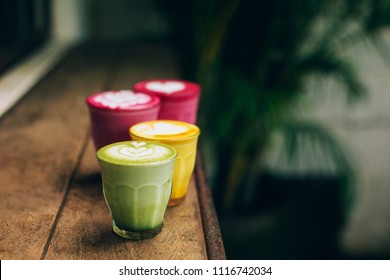 Trendy multicolored lattes. Beetroot, avocado and turmeric tastes with latte art.