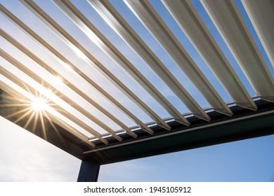 Trendy outdoor patio pergola. the sun's rays pass through the metallic structure