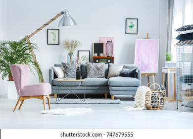Trendy pastel studio with pink painting on easel and watercolor pictures