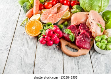 Trendy pegan diet - vegan plus paleo diet food concept, many fresh vegetables, fruits, raw beef and chicken meat, salmon fish, white wooden background top view copy space